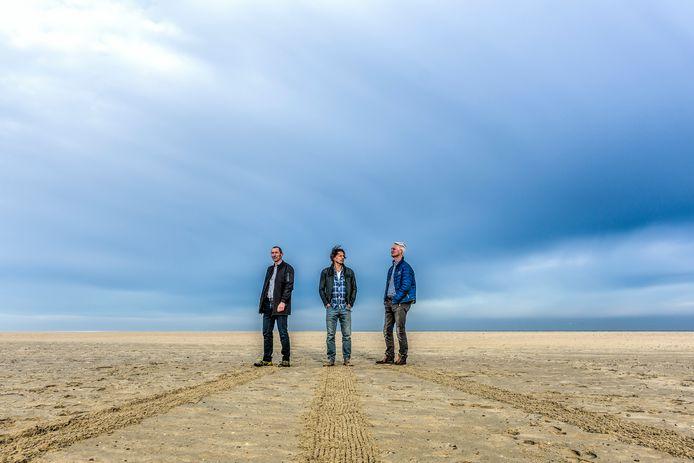 René Bosma, Remko Delfgaauw en Ron van Jeveren in 2017 op het strand van de Brouwersdam. De mannen die eerder schitterden met een megagraancirkel en dito zandtekening zetten als Extinction Rebellion Zeeland dit weekend een protestoproep in het zand. (archieffoto)