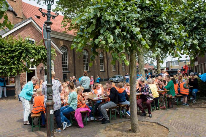 Kinderen van OBS De Zwaluw lunchen op het Kerkplein met wentelteefjes.