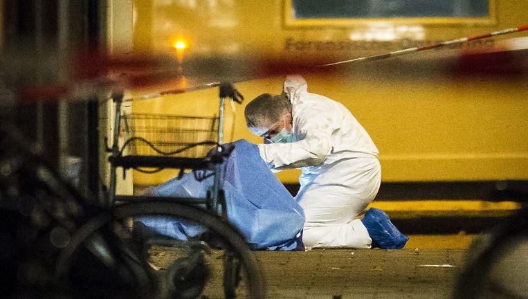 Een forensisch expert doet onderzoek bij het lichaam van het slachtoffer. Beeld anp