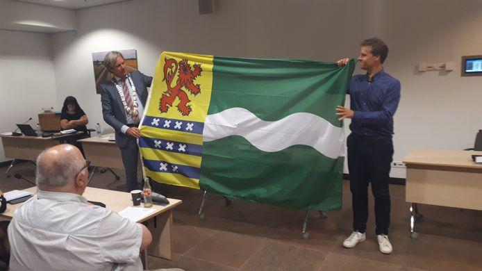 Burgemeester Foort van Oosten (l) en wethouder Martijn Hamerslag presenteren aan het eind van een marathonvergadering van de raad de nieuwe gemeentevlag