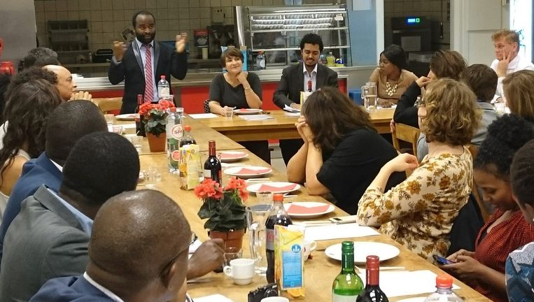 Kiza Magendane spreekt minister Ploumen (naast hem) en andere dinergasten toe. Beeld Fleur van Diesel