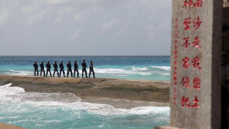 Chinese militairen patrouilleren op een van de Spratley: in China: Nansha) eilanden. Tekst op de steen: 'Nansha is onze nationale grond, heilig en onschendbaar.' Beeld reuters
