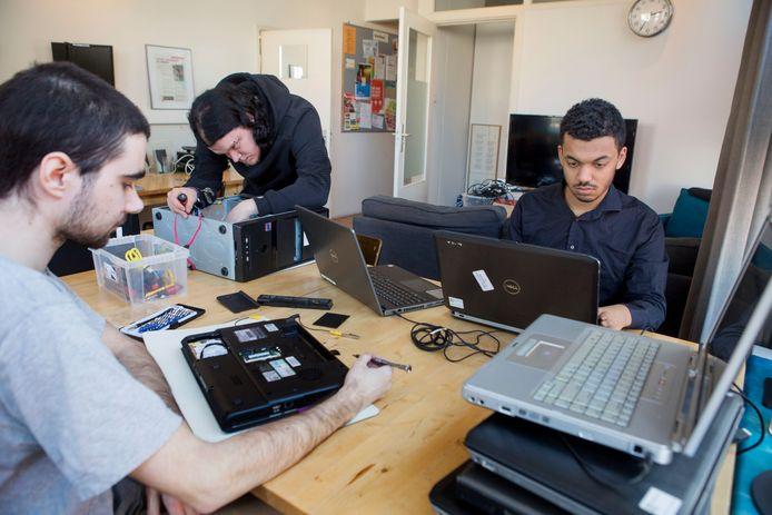 Yannick Coolen repareert het binnenwerk van een computer (staand) en Rafaël Klein beantwoordt vragen van klanten.
