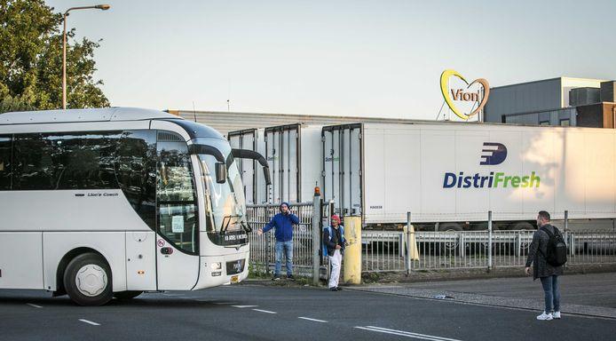 Een touringcar met buitenlandse medewerkers arriveert bij het slachthuis van Vion in Apeldoorn.  Het dragen van mondkapjes in de bussen is verplicht.