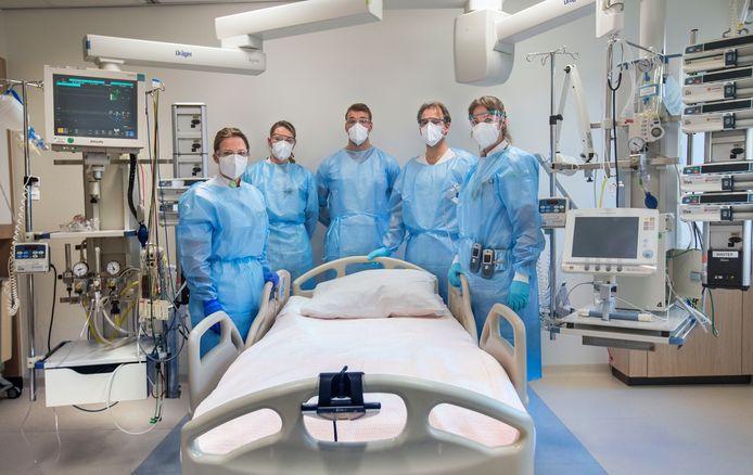 Een ic-bed in het HagaZiekenhuis met een deel van de apparatuur en medewerkers die daarbij nodig zijn. vlnr Denise van der meer ic-buddy, Joëlle van Domburg ic-verpleegkundige, Wesley Jetten, arts assistent ic, Tim Jansen intensivist, Mira Jentink ic-verpleegkundige.