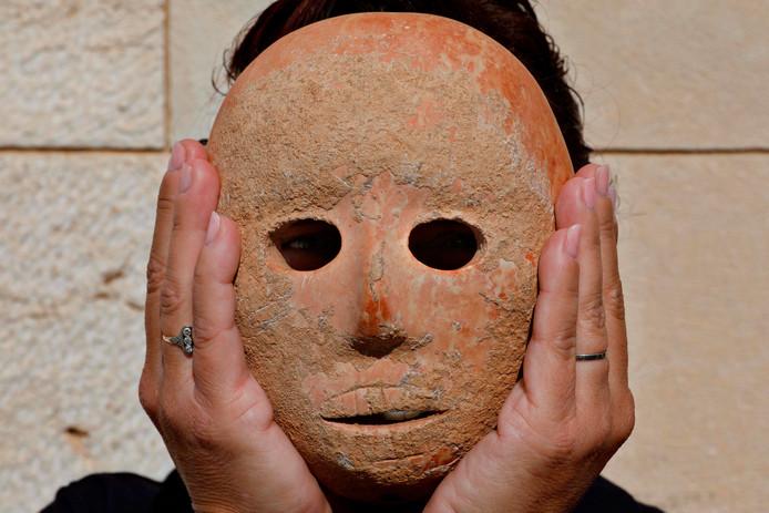 Archeologe Ronit Lupu houdt de bijzondere vondst voor haar gezicht.