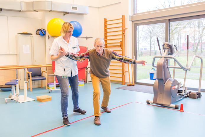 Fysiotherapeute Alette de Pooter oefent met een patient de 'grote bewegingen'.