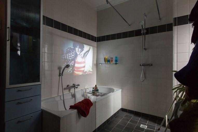 Een film uit het archief van filmmuseum EYE wordt geprojecteerd op de badkamermuur van een Museumstraatdeelnemer. Beeld Museumstraat