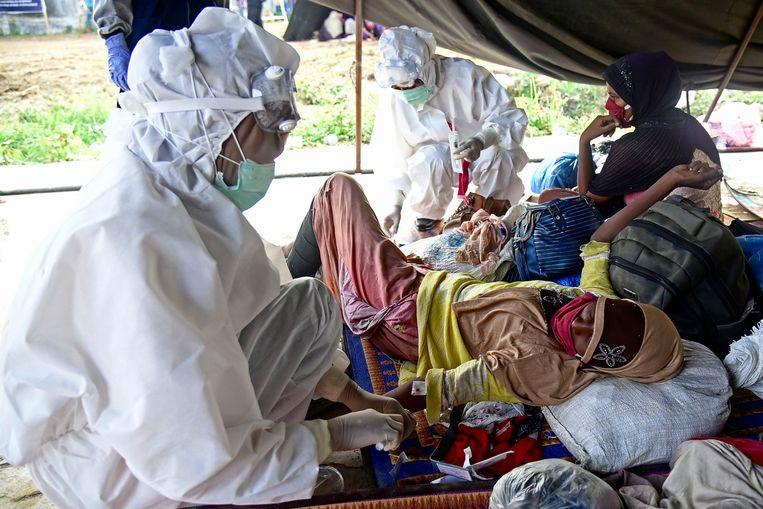 Een van de bootvluchtelingen wordt door medici onderzocht.  Beeld AFP