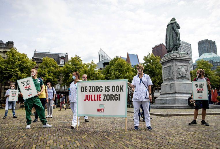 Zorgverleners voeren actie op het Binnenhof voorafgaand aan de hoofdelijke stemming over een motie van Geert Wilders (PVV) voor een salarisverhoging voor zorgmedewerkers.  Beeld ANP