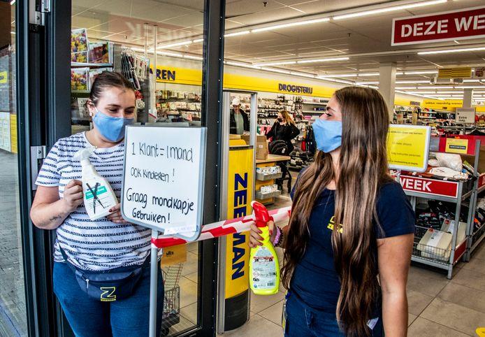 Lisa de Visser (r) en winkelchef Kelly de Jong staan klanten met desinfectie op te wachten en vragen om een mondkapje op te doen.