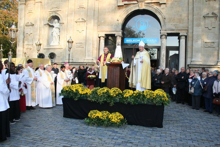Iedereen klaar voor het vertrek, kaars in de hand onder het wakend oog van de hulpbisschop