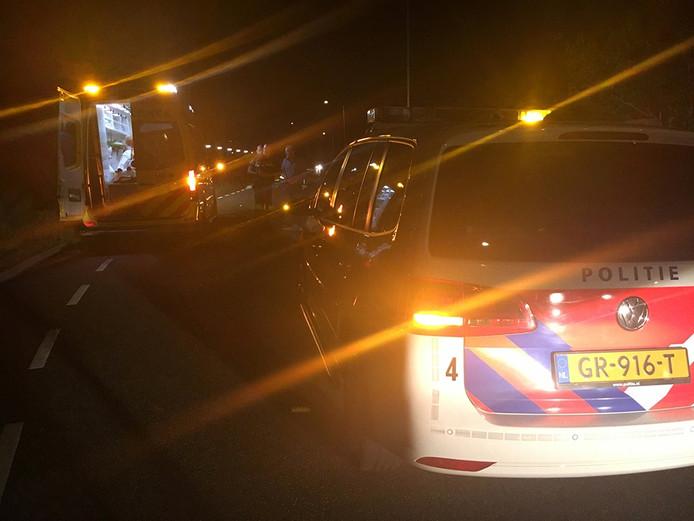 De politie bekijkt de schade aan de voertuigen. In de ambulance wordt één van de inzittenden onderzocht.