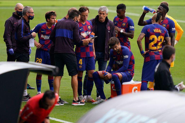 Ontluisterend beeld tijdens de drinkpauze: assistent Sarabia geeft de uitleg, coach Setién kijkt er enkel naar. Piqué draait het hoofd weg.