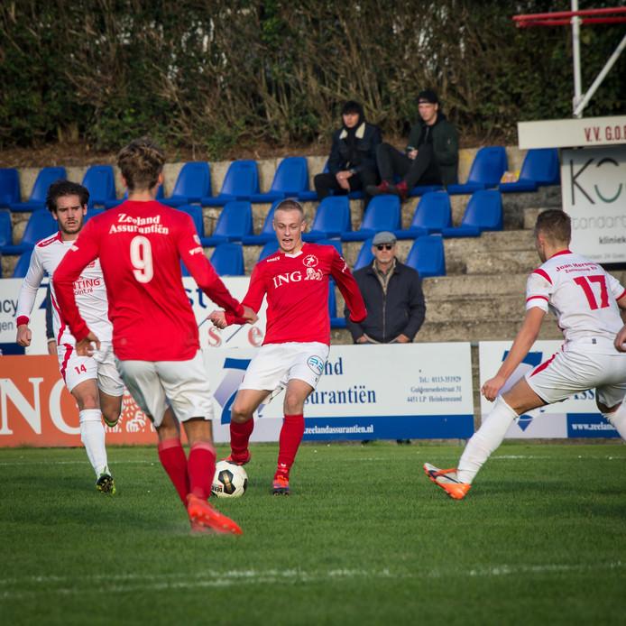 Klaas van Hecke (midden) van Goes speelt spits Steve Schalkwijk (nummer negen) aan.