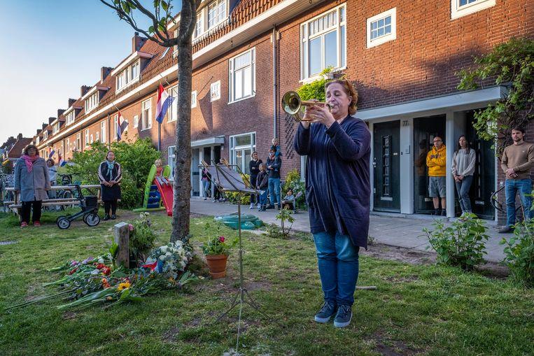 Dodenherdenking in de Pythagorasstraat in Amsterdam. Petra Seel blaast de taptoe, bewoners van haar straat luisteren. Beeld Patrick Post
