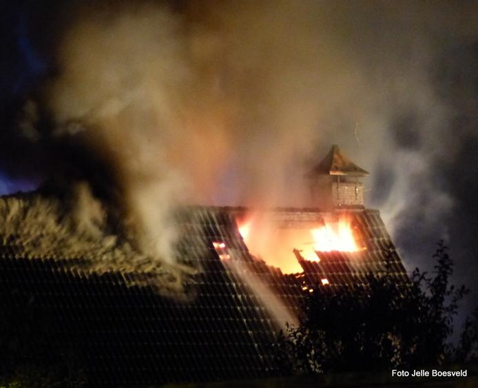 De vlammen sloegen na de blikseminslag uit het dak van de woning in Neede.