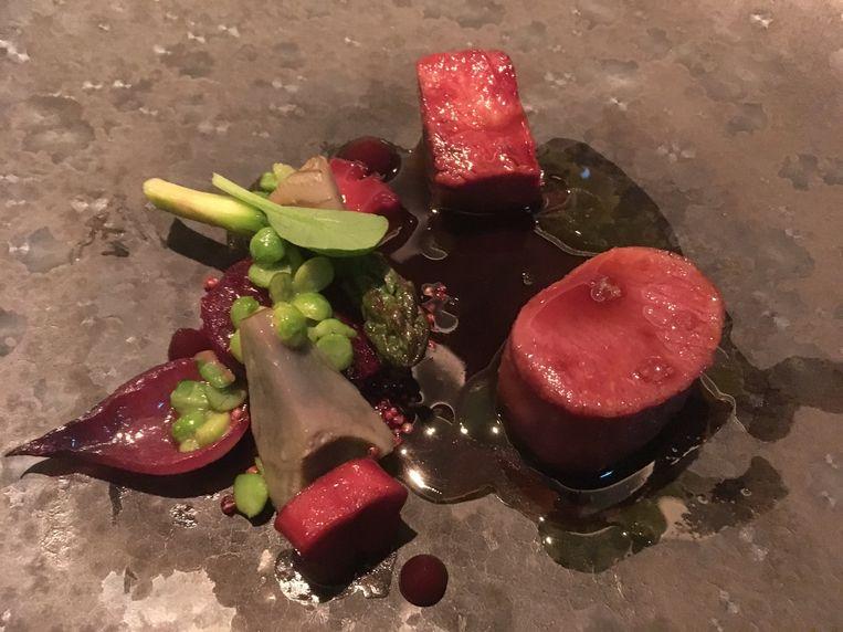 In klei gebakken lamsschouder met voorjaarsgroenten en saus met hibiscus. Beeld Mac van Dinther