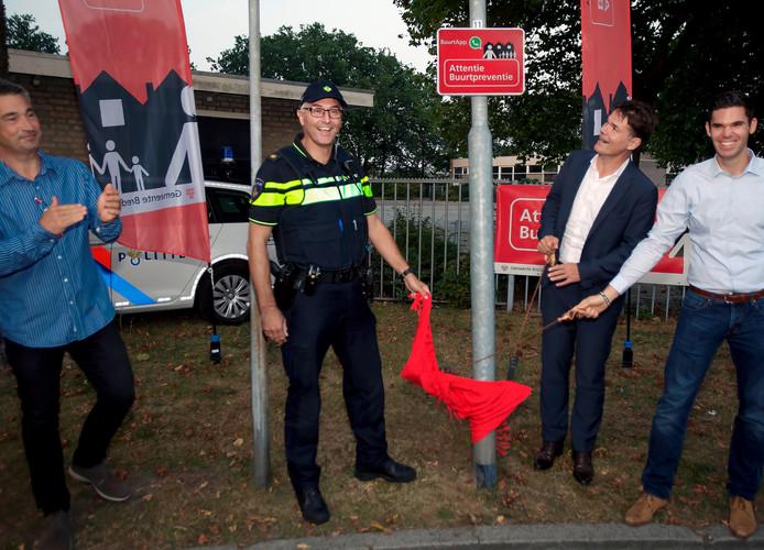 Burgemeester Depla van Breda onthult het bord van de eerste Buurtapp die onder Buurtpreventie Breda opereert. Uiterst links Chris Aarts.