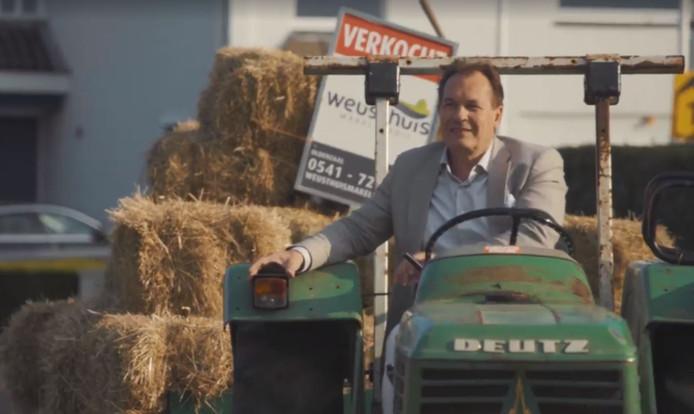 Luc Weusthuis vervoert zijn personeel op een platte kar naar de plaats waar de makelaar een nieuwe vestiging opent: In Losser.