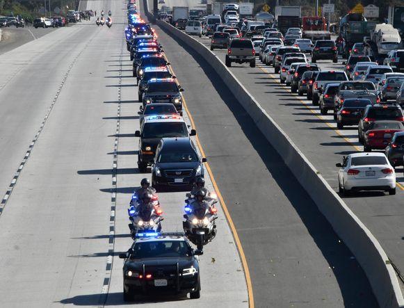 De politieman werd geëerd met een colonne politiewagens achter de lijkwagen.