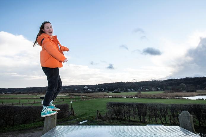 Bijschrift: Ilse van der Hogen bij de plek waar zich 210.000 jaar geleden een klimaatverandering manifesteerde. Het ijs kwam tot hier en duwde de grond voor zich uit. Zo ontstond - hier op de achtergrond te zien - de heuvelrug.   Foto Paul Rapp
