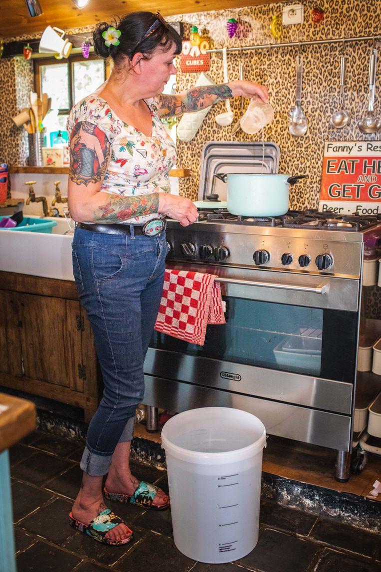 Sandra gebruikt in de keuken een bidon met water om te koken.