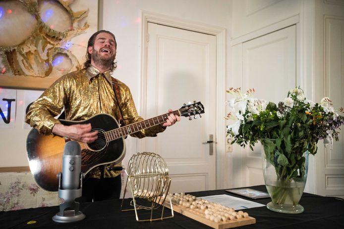 Tim Akkerman in zijn woonkamer tijdens een potje online bingo. De maatregelen omtrent het coronavirus inspireerden de zanger om de spelavonden te organiseren. De winnaars kregen een liedje cadeau. Nu is het tijd voor de café tour.