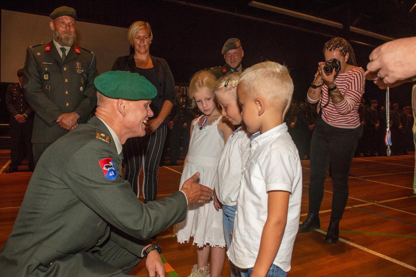 Brigadegeneraal Jan Swillens reikt vrijdagochtend aan Gemma, Madeleyne (midden) en haar broertje Zegert de eerste kindermedailles uit.