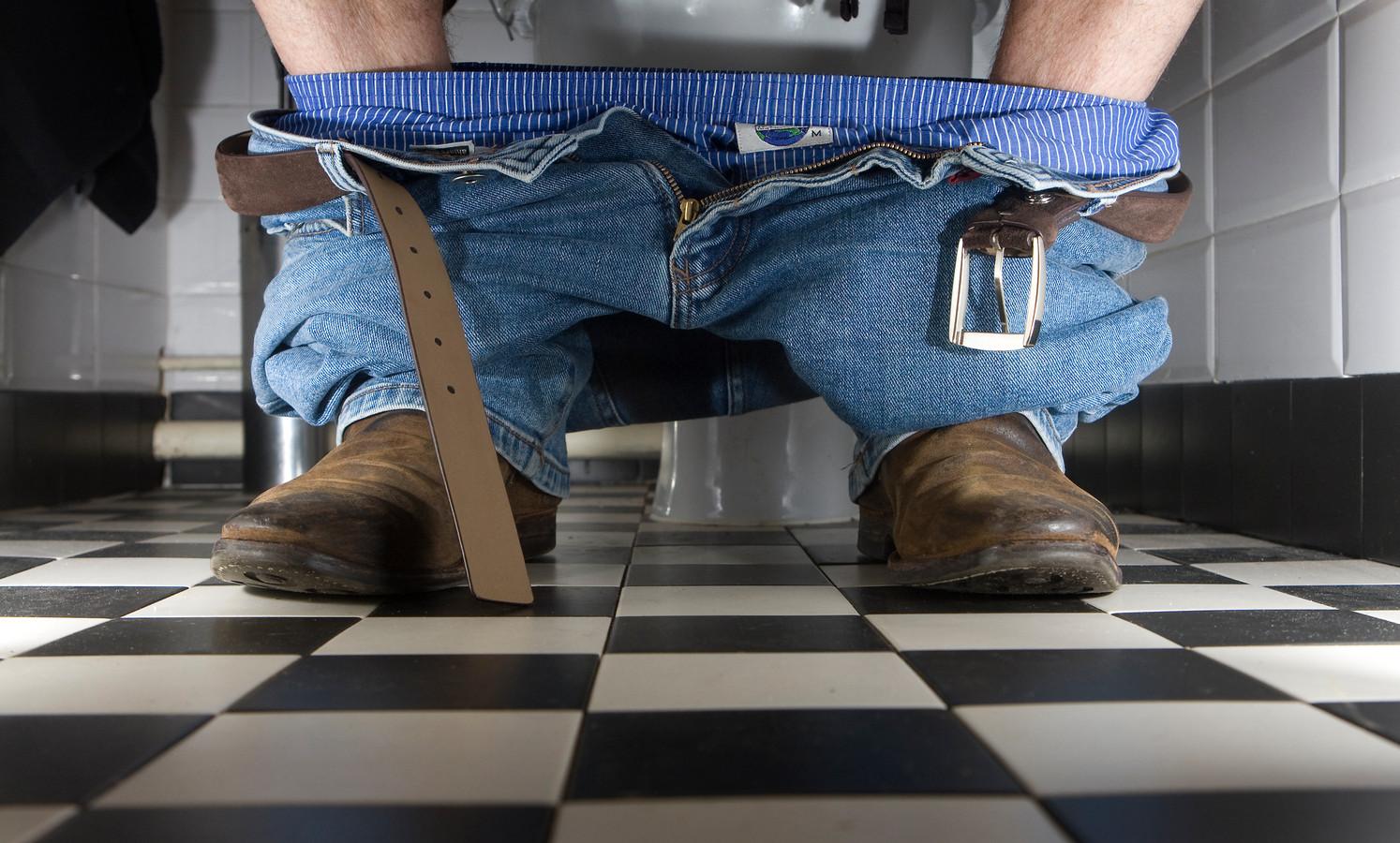 Een man zit op het toilet. Foto ter illustratie.
