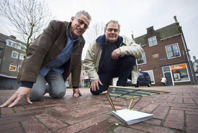 Wim Hofstede en Henk Scholten van de Vrienden van Huissen met een schaalmodel van het Odeon op de Huissense Markt.