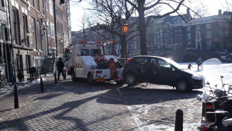 Auto's worden weggesleept op de Keizersgracht om het publiek ruim baan te geven. © Willem de Wit Beeld