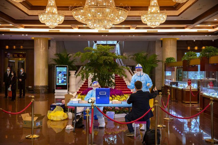 Een buitenlandse journalist ondergaat in zijn hotel een virustest voorafgaand aan het Nationale Volkscongres.  Beeld Mark Schiefelbein / AP