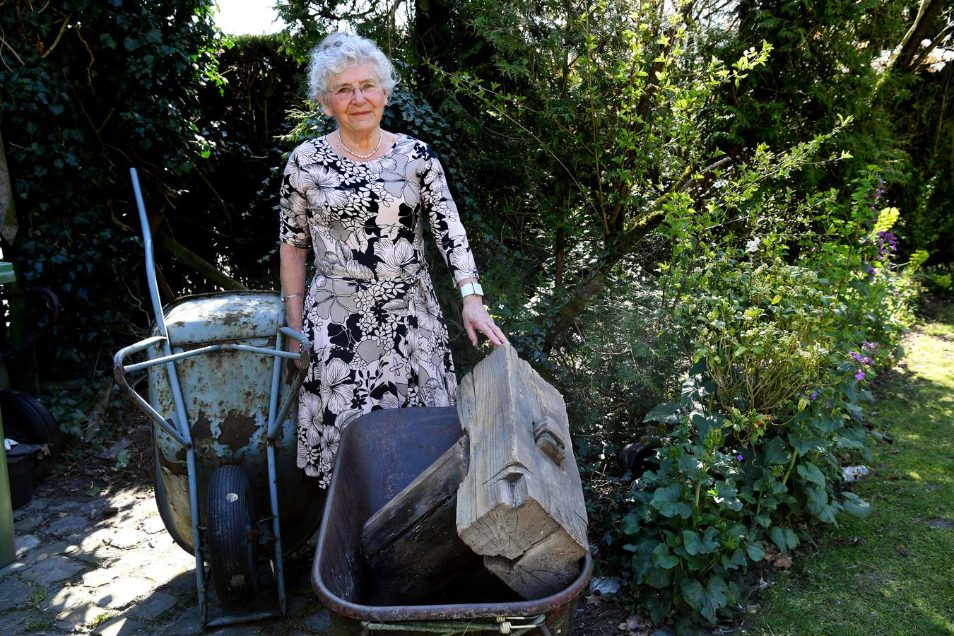 Isabel Bakker staat trots bij de resten van een unieke funderingstechniek die bewaard is gebleven in de tuin. Een levende herinnering aan haar Dick.