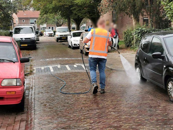 Een medewerker van de gemeente spuit de Vanenburgstraat in Wageningen schoon na een steekpartij.