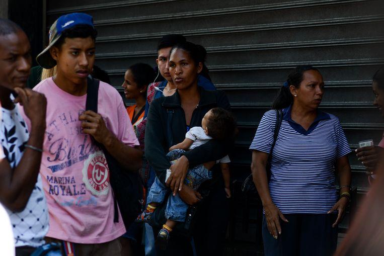 Venezolanen staan in de rij om eten te kopen. Beeld null