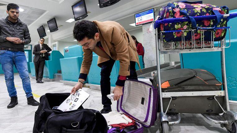 Een reiziger uit Libië moet zijn laptop overpakken naar zijn in te checken bagage. Beeld afp