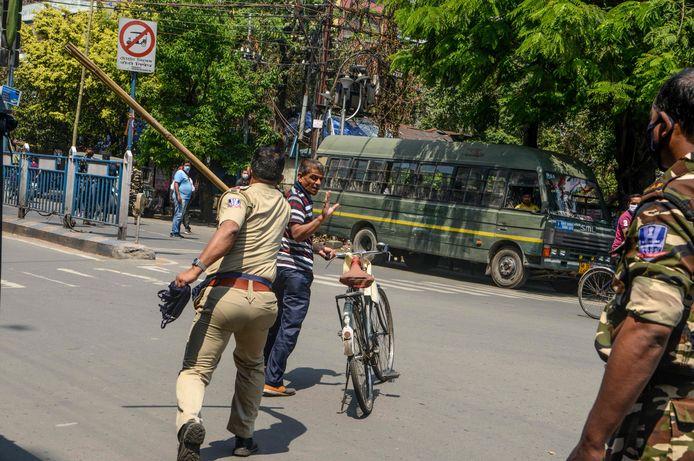 Un policier tente de frapper un homme avec un bâton à  Siliguri, dans l'État indien du Bengale-Occidental, le 24 mars 2020.