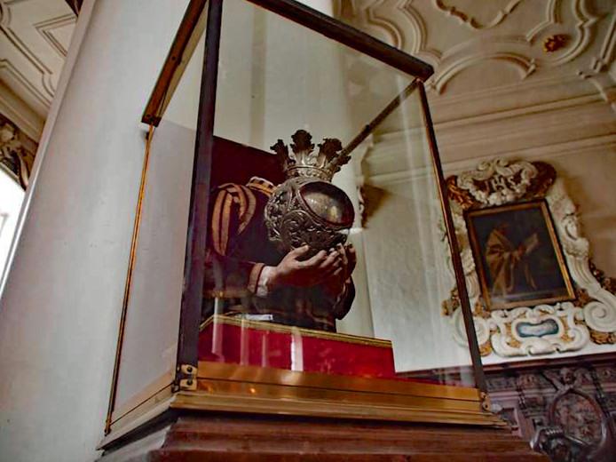 Het hoofd van de jonge, standvastige Sint-Justus wordt vastgehouden door twee kunsthanden.