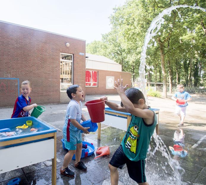 Kinderen van basisschool de Salto in Rijssen spelen met watertafels tegen de hitte.