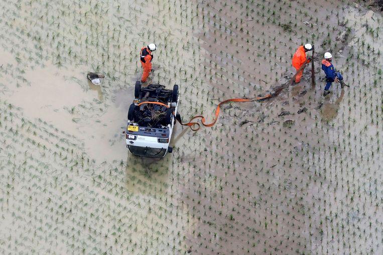 Een op zijn kop belande auto wordt weggesleept uit een rijstveld bij Hitoyoshi. Beeld AP