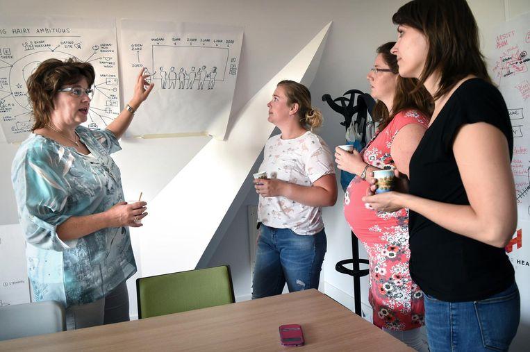Enige manager Hanny Veenhuis (links) overlegt met wijkverpleegkundigen. Ze stuurt bij Sensire in haar eentje tweeduizend zorgverleners aan. Beeld Marcel van den Bergh / de Volkskrant