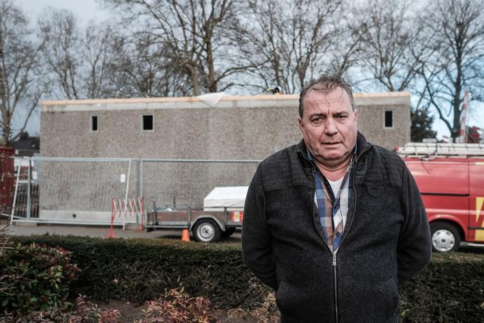 Frank Bloem kijkt vanaf zijn woonkamer uit tegen een groot relaisgebouw. s