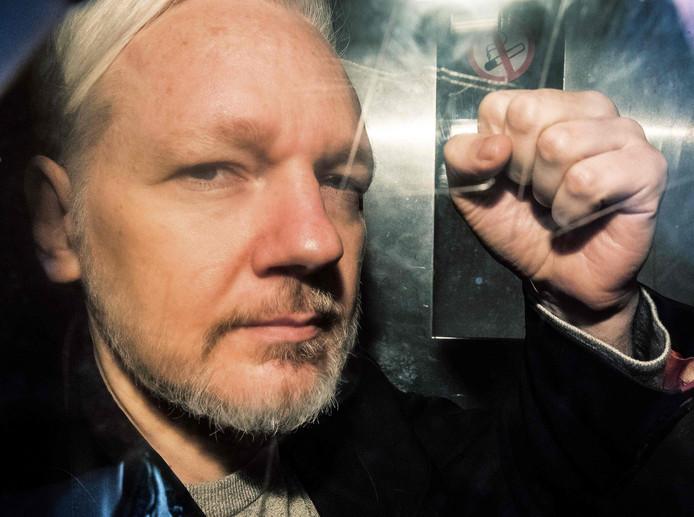 Julian Assange in een politiebusje voor zijn proces op 1 mei in Londen, waar hij tot 50 weken celstraf zou worden veroordeeld.