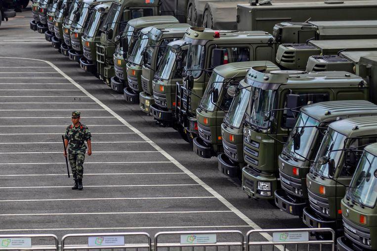 Een militair van het Chinese Volksleger loopt donderdag langs militaire vrachtwagens in een sportstadion in Shenzhen.   Beeld null