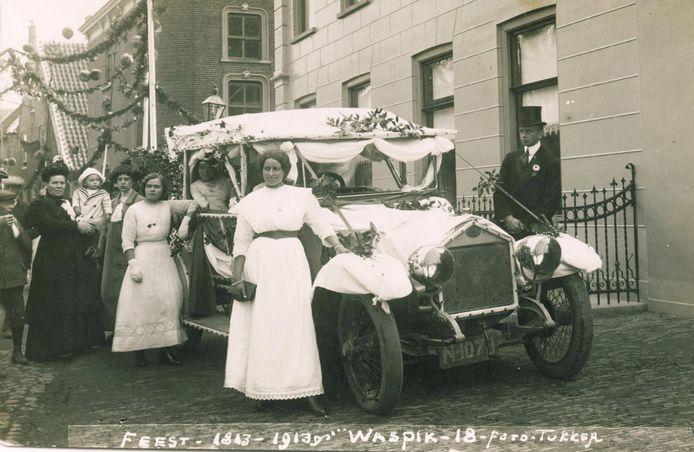 Dick de Roon bij de auto van de familie tijdens Onafhankelijkheidsfeest in 1913 . De vrouw in de witte jurk op de voorgrond met haar hand op het spatbord is een dochter van notaris Middelkoop. De jonge vrouw leunend met haar arm op de auto is dochter Cornelia.