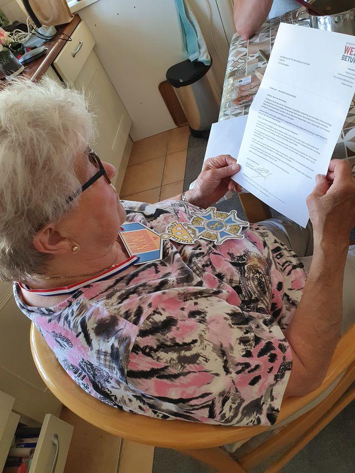 Netty Verbeek geeft het lintje aan haar moeder.