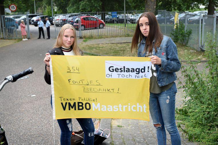 25 juni 2018: Twee leerlingen maken op een schoolvlag hun protest tegen de gang van zaken kenbaar.  Beeld Marcel van den Bergh / de Volkskrant