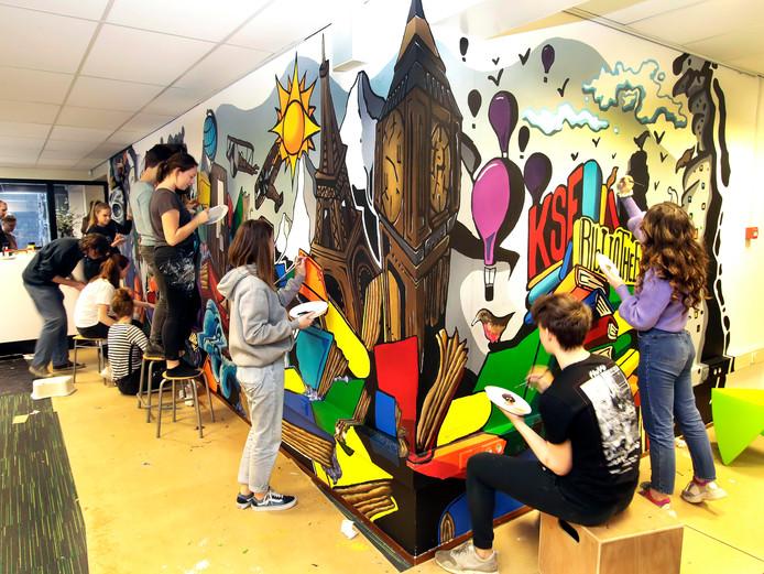 Leerlingen van de KSE druk in de weer met een groot kunstwerk aan de wand van de kantoorruimte bij de hoofdingang van het gebouw.