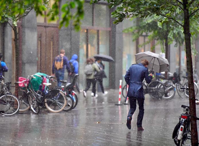 Een voorbijganger loopt door een stevige regenbui op de Turfmarkt in Den Haag.